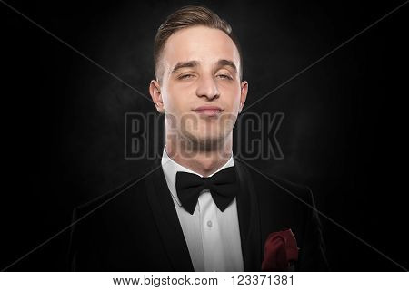 Highly successful business man in suit over dark background.