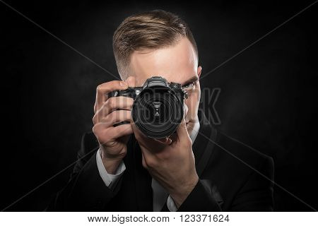 Photographer with camera on a dark background.
