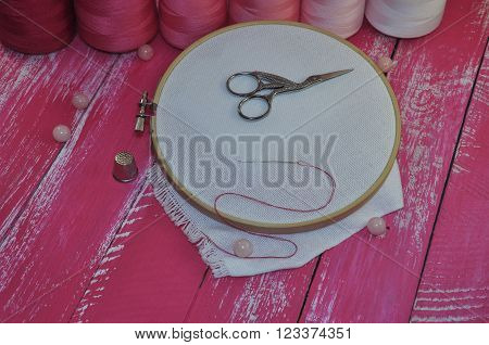 background bobbin canvas cloth crafts handmade hobby hoop iron needle object pink reel scissors thimble thread vintage wood