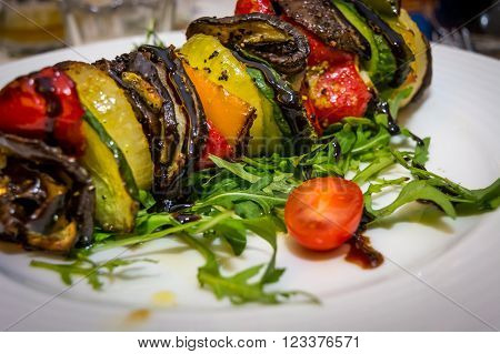 Hot vegetarian shashlik with courgette, aubergine, onion, red pepper and arugula