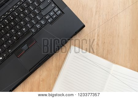 Laptop and notebook on wood table in warm tone