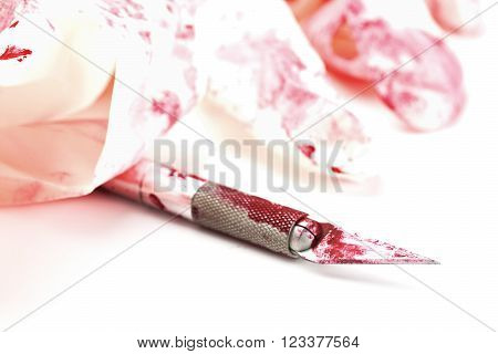 Stainless steel scalpel with blood and rubber gloves - selective focus on tip of blade