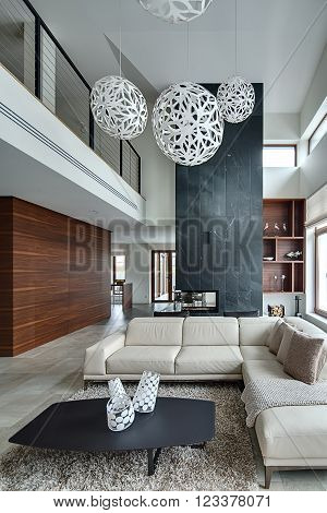 Hall in a modern style with light walls and big white round decorative lamps at the top. There is a beige sofa with pillows and plaid, dark table with three decorative vases, two black armchairs behind the sofa. Under them there is a brown-beige carpet.