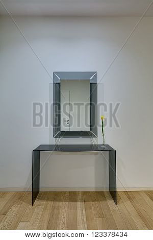 Light wall with mirror with frosted glass frame on it. Their is a frosted glass table with yellow tulip in glass vase under mirror. White door reflected in the mirror. On the floor there is a light parquet.