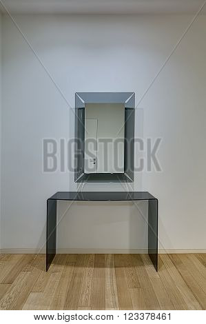 Light wall with mirror with frosted glass frame on it. Their is a frosted glass table under mirror. White door reflected in the mirror. On the floor there is a light parquet.