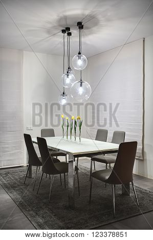 Room with light walls. On the floor there are gray tiles and a gray carpet. On the carpet stands table with frosted glass tabletop and chromed legs. On the table stand 5 glass vases with yellow tulips. There are 6 gray chairs around the table.