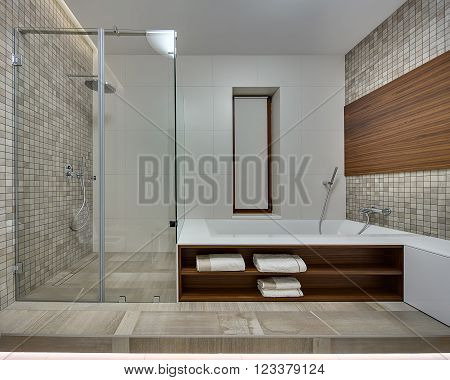 Bathroom in a modern style with light tiles on the back wall. Side walls is decorated with brown-beige mosaic  and a wooden panel. On the right there is a white bath with wooden niches. There are towels in the niches. On the left wall there is a shower ca