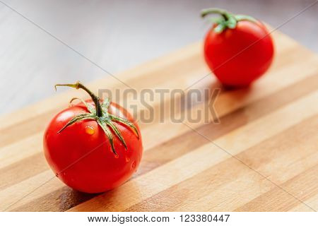 large and red tomato with green leaves on a bamboo board ** Note: Soft Focus at 100%, best at smaller sizes