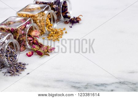 Front view of herbs and spices in glass jars spilling onto white marble stone. Selective focus on second jar with rose buds.