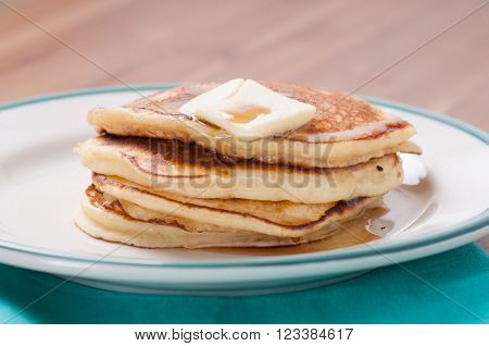 delicious pancakes in a stack with melting butter and maple syrup
