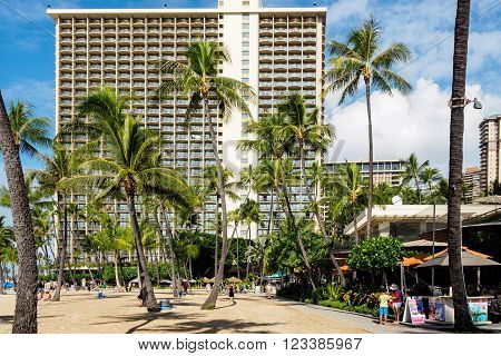 Waikiki, Honolulu, Hawaii, USA - December 13, 2015: Waikiki Beach and palm trees on a sunny afternoon. The beach is not as crowded with people on this occasion. The building in the distance is the Hilton Hotel.