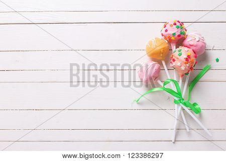 Cake pops on white wooden background. Selective focus.Place for text.