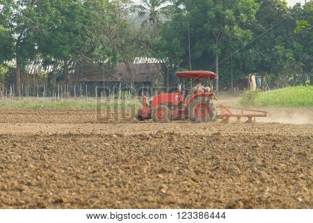 tractors plow the farm in local country ** Note: Soft Focus at 100%, best at smaller sizes