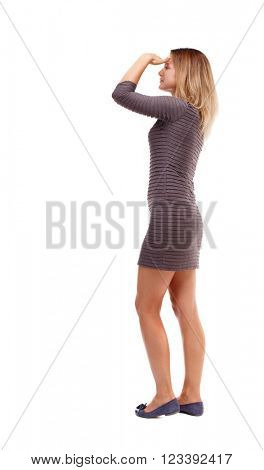 back view of standing young beautiful  woman.  girl  watching. Rear view people collection.  backside view of person. The girl in a brown dress standing sideways putting his hand to his eyes.