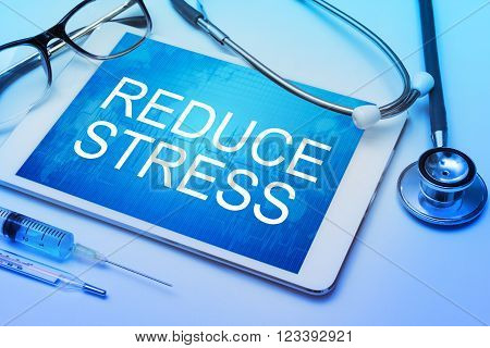 Reduce Stress word on tablet screen with medical equipment on background
