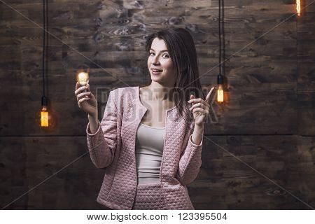 Beautiful young smart woman in a suit burning light bulb in his hand which signifies inspiration or a new idea