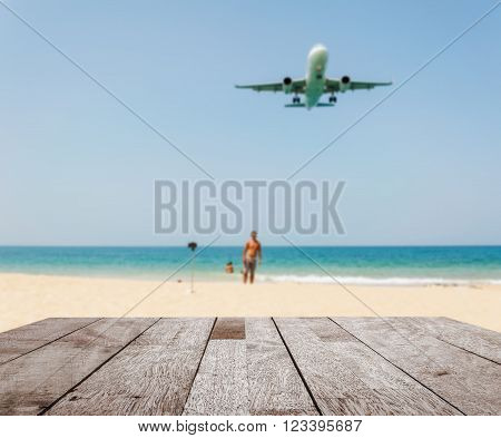 Wood floor top on blurred blue sea and white sand beach with some people and plane, Can be used for display or montage your products