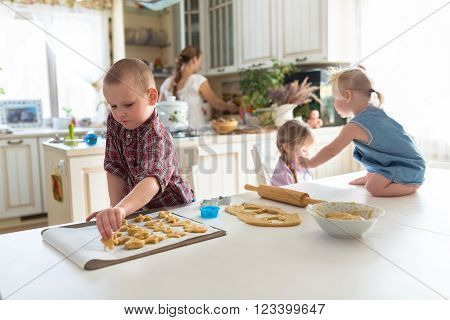 children with her mother preparing cookies independent children large family. casual lifestyle photo series in real life interior
