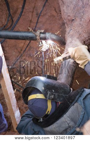 The workers make the sidebar of the gas pipe to the gas pipeline welding
