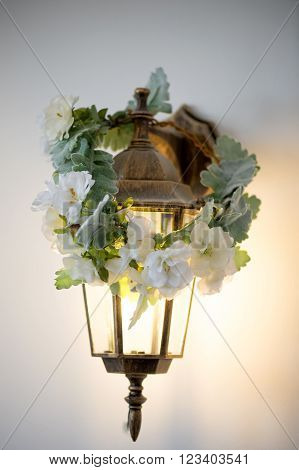 Golden sconces lantern with wreath. Warm and cozy light