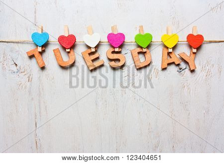 word Tuesday from wooden letters with colored clothespins on a white wooden background