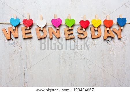 Wednesday word from wooden letters with colored clothespins on a white wooden background