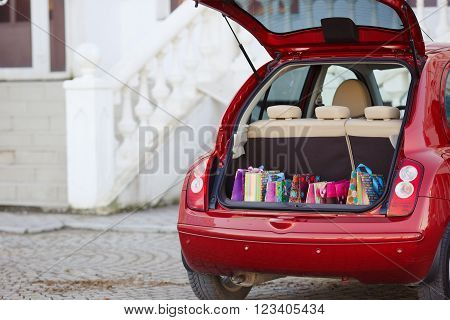 The red car is a hatchback,the seats beige color,stands alone near the entrance to the shopping centre with an open trunk lid,filled with colored paper bags for shopping ahead