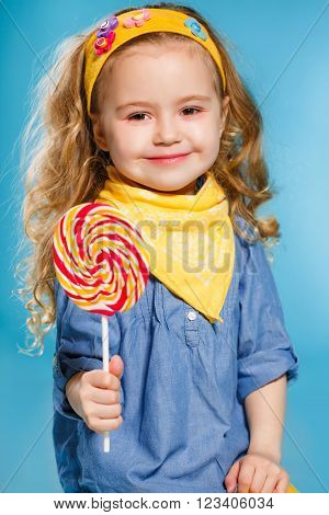 Funny little girl with long, curly hair,with a yellow handkerchief around her neck, a sweet smile,is dressed in a blue shirt and yellow pants,posing in Studio standing against a blue background, holding a large,round, colourful Lollipop