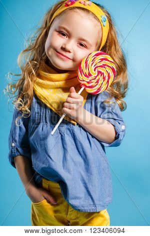 Funny little girl with long, curly red hair,with a yellow handkerchief around his neck, a sweet smile,is dressed in a blue shirt and yellow pants,posing in Studio standing against a blue background, holding a large,round, colourful Lollipop