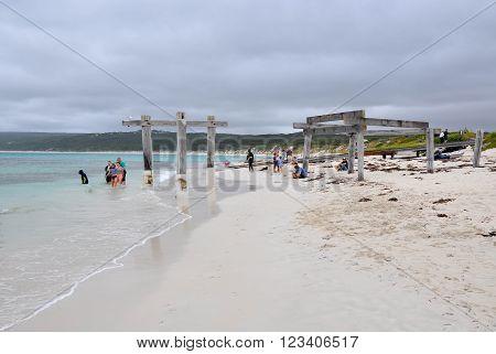HAMELIN BAY,WA,AUSTRALIA-JANUARY 17,2016: People petting wild stingrays and jetty ruins on the beach under stormy skies in Hamelin Bay, Western Australia.