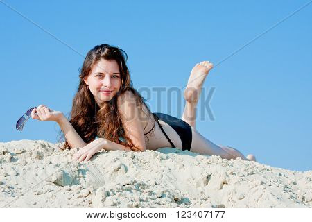 young beautiful woman in a swimming suit on a background blue sky