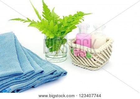 Shampoo and Shower gel put in ceramic basket on white background. Shampoo Shower gel bottles with blue cloth and green leaves in a glass of water.