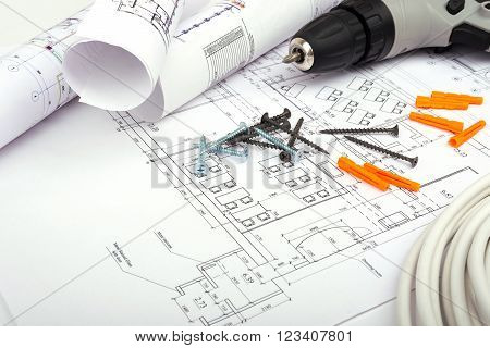 Architecture plan and rolls of blueprints with screws and electric screwdriver. Building concept
