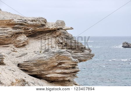 Layered limestone cliffs at White Cliff Point with Indian Ocean waters on a stormy day in Hamelin Bay, Western Australia.
