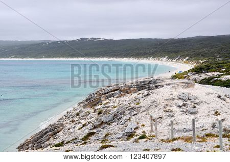 View over Hamelin Bay from the limestone bluff at White Cliff Point with turquoise Indian Ocean waters and vegetated dunes  under dark, stormy skies in Western Australia.