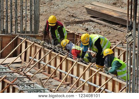 MALACCA, MALAYSIA -FEBRUARY 23, 2016: Construction workers fabricating floor slab reinforcement bar at the construction site in Malacca, Malaysia.