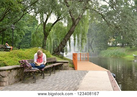 RIGA / LATVIA - July 27 2013: Young woman write something in her notebook on river bank in city park of Riga