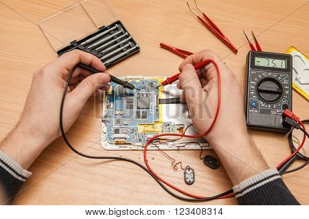 Master Is Looking For The Fault Of The Tablet With A Multimeter. Hands Of A Top View.
