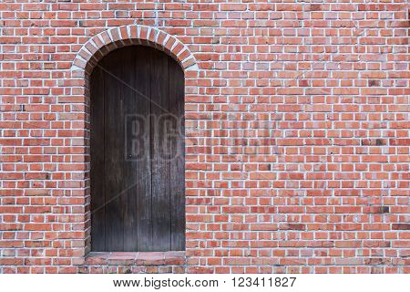 Old red brick wall with wooden door.