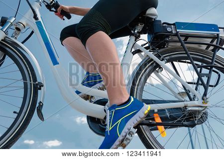Riding e-bike or electric bicycle shot against blue sky clean air concept