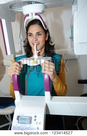 Young woman having dental panoramic x-ray in dental center by hightech digital equipment.
