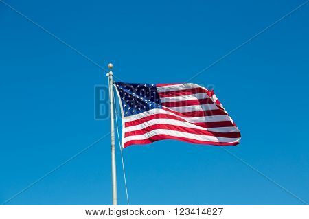 American flag waving in the wind on a blue sky