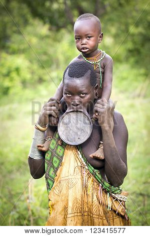 Kibish, Ethiopia, Africa - Nov 9: Tribal woman with lip plate and child on her shoulders poses for her portrait on Nov 9 2015 in Kibisch, Ethiopia.