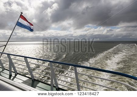 Wadden Sea with Dutch flag and wake as seen from the ferry