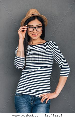 Just take a look at this cutie! Beautiful young Asian woman in hat adjusting her glasses and looking at camera with smile while standing against grey background