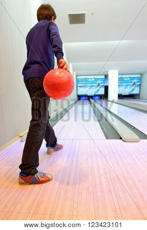 Young boy prepared on bowling lane, sport an leisure