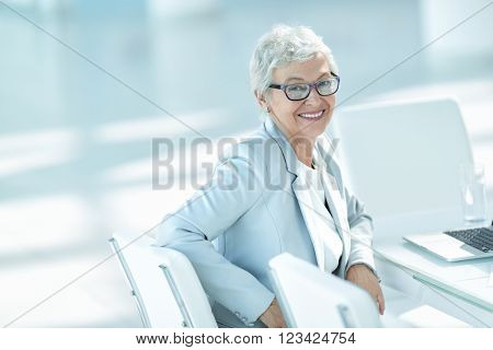 Elderly woman with laptop in office