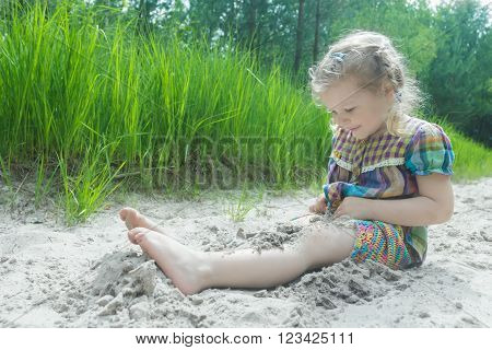 Little girl is playing on beach dune and burying herself in white sand at summer pinewood background