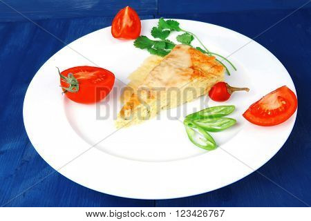 food : vegetable casserole triangle on white plate with pepper and tomatoes on blue table