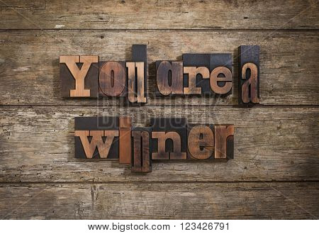 you are a winner, phrase written with antique letterpress printing blocks on rustic wooden background